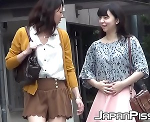 Petite Japanese girls are pissing in a public bathroom